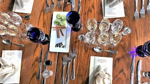 Several shot glasses and stemmed tequila glasses atop a wood table with place settings for 4 Guests