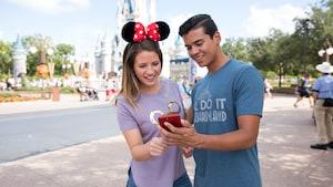 Una pareja mira un teléfono móvil, con Cinderella Castle en el fondo