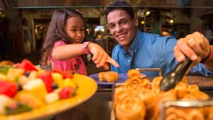 A man and his daughter select Mickey waffles from a breakfast buffet