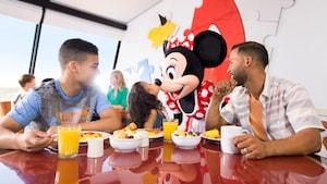 Minnie Mouse saluda a una familia de 3personas mientras disfrutan su desayuno