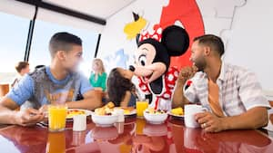 Minnie Mouse greets a family of 3 as they enjoy breakfast