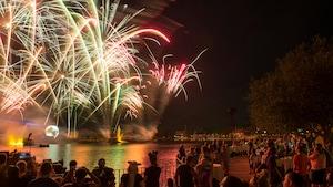 Una multitud reunida en torno a World Showcase Lagoon para mirar el espectáculo de fuegos artificiales nocturno en Epcot