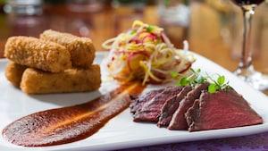 Un plato con carne de res rebanada y un acompañante de croquetas