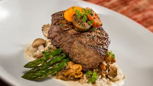 A thick cut of steak, served with asparagus, mushrooms and tomatoes