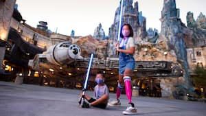 Adult and child posing with lightsabers in Galaxy's Edge
