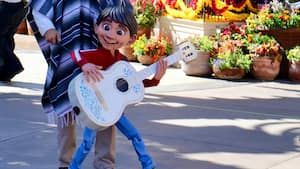 A man in a Mexican poncho operates a life size puppet of Miguel from the movie Coco