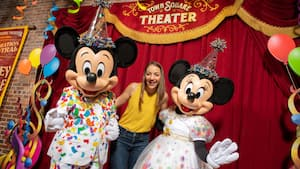 Com trajes de festa, Mickey Mouse e Minnie Mouse posam com uma Visitante no Town Square Theater