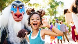 Rafiki holds the hand of a smiling young girl wearing a Minnie ears headband