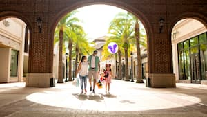 Wearing face masks, a mom, dad and their daughter, who is holding a large Minnie plush and a Mickey balloon, walk under an arch at Disney Springs