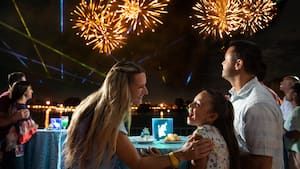 A family has a great time watching fireworks while eating dessert