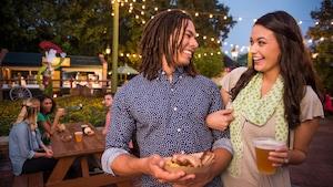 Casal caminhando de braços dados e saboreando um prato no Epcot International Flower and Garden Festival