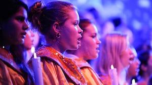 Integrantes do coral segurando velas e cantando na Candlelight Processional