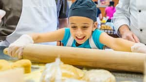 A young girl rolling dough with a rolling pin