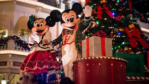 Dressed in holiday attire, Mickey Mouse and Minnie Mouse wave from in front of a Christmas tree