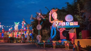 People stand near the entrance of Toy Story Land at night
