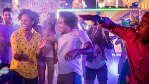 2 jóvenes adultos bailan juntos en una fiesta al aire libre en Dinoland