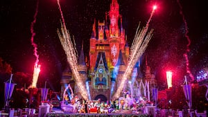 A festive Cinderella Castle illuminated at night with lasers and fireworks as over a dozen Disney Characters wave from in front, dressed for the holiday season, along with Mickey and Minnie in a sleigh