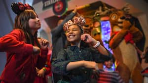 Two girls wearing Mickey ears dance while reindeer stand in the background