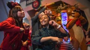 Duas meninas usando orelhas do Mickey dançam com renas ao fundo