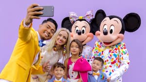 A father takes a selfie of himself and his family as they pose with Mickey and Minnie Mouse