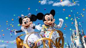 Mickey e Minnie em uma alegoria em frente ao Cinderella Castle com confete voando pelo ar