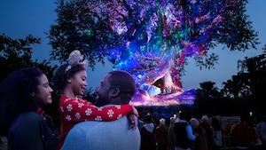 Una madre y un padre abrazan a su hija frente al Tree of Life en el Parque Temático Disney's Animal Kingdom