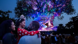 A mom and dad hugging their daughter in front of the Tree of Life at Disney's Animal Kingdom theme park