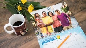 A calendar featuring a family photo taken in front of Cinderella Castle, with an inset image of Buzz Lightyear and Woody