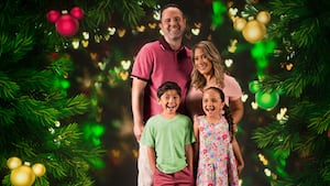 A family superimposed on a background of decorated Christmas trees
