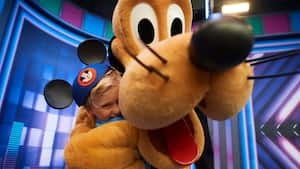 Pluto hugging a young boy wearing Mickey ears