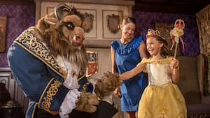 The Beast holding the hand of a young girl in a Belle costume as her mother looks on