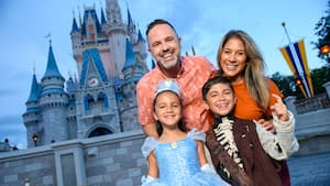 A girl in a Cinderella dress and boy in a skeleton costume posing with their parents in front of Cinderella Castle