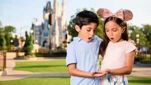 A young girl and boy respond with wonder to an image of Tinker Bell situated in the palm of their outstretched hands.