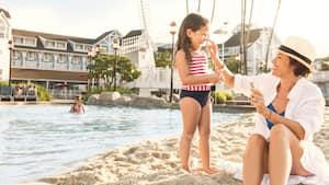 A mother puts sunscreen on her daughter's nose as they sit poolside at Stormalong Bay at Disney's Yacht Club Resort