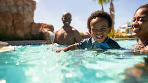 Mom and dad swim with toddler in Disney's Riviera Resort pool