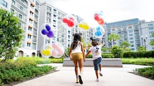 A young boy and girl holding hands and Mickey balloons as they skip through Riviera Resort