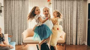 A father happily carries his young daughters on his hips as they twirl wands within their Disney Resort hotel room