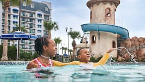 A brother and sister splash in the pool at Disney's Riviera Resort.