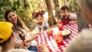 Una madre se ríe mientras sus 3hijos comen barras de helado de Mickey Mouse en una mesa para pícnic