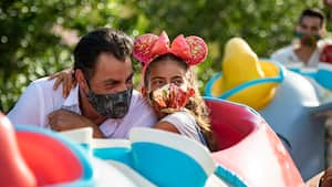 Daughter and Father enjoy riding Dumbo the flying elephant with face coverings
