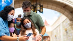 Family stands together in Disney's Magic Kingdom Park with face coverings looking at cell phone for planning purposes