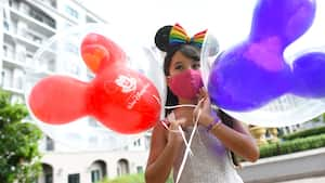 Young girl stands in front of Disney's Rivera Resort with two Mickey balloons