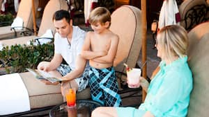A couple and their son rest on lounge chairs by the pool while sipping tropical beverages