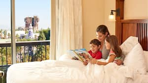 A woman reads to 2 children in a bed near a window with a view of Guardians of the Galaxy Mission  BREAKOUT