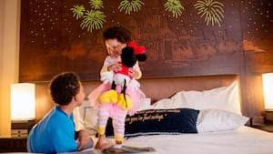 A girl holds a Minnie Mouse doll on a bed with a boy
