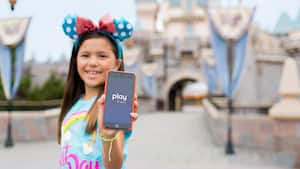 A young girl wearing Mickey Ears holds up a smartphone with the Play Disney Parks app open