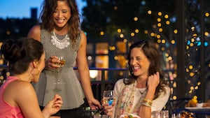 Three women laugh as they drink at a table
