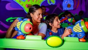 Una madre y su hijo apuntan cañones espaciales en Buzz Lightyear's Space Ranger Spin