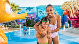 A teen girl and her young brother have fun in the themed pool at Disney's Art of Animation Resort