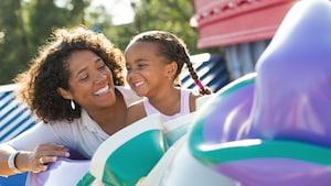 Una mamá y su hija sonríen juntas mientras disfrutan Dumbo the Flying Elephant en el Parque Temático Magic Kingdom
